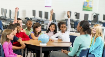 Diverse group of elementary school students in a classroom.