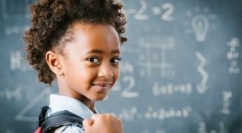 Cute little African school girl in classroom.